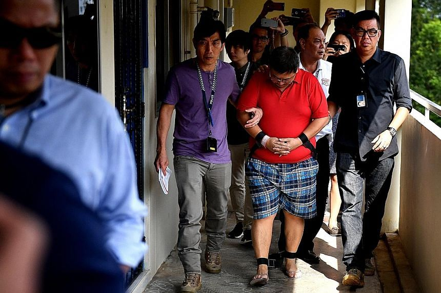 Woodlands double-murder suspect Teo Ghim Heng being escorted by police to his flat at Block 619 Woodlands Drive 52 on Feb 10, 2017. Teo, who was mired in debt, said he decided to end the lives of his pregnant wife and daughter because he did not want