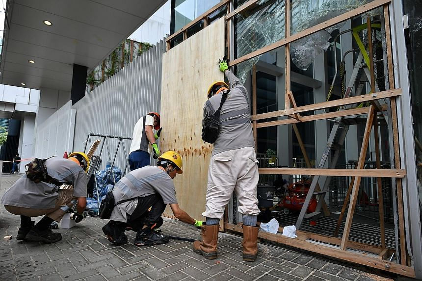 Police at the Legislative Council Complex yesterday. China has increasingly been critical of what it calls Western instigation to stir trouble. ST PHOTO: LIM YAOHUI Workers putting up a wooden hoarding yesterday to cover shattered glass panels at the