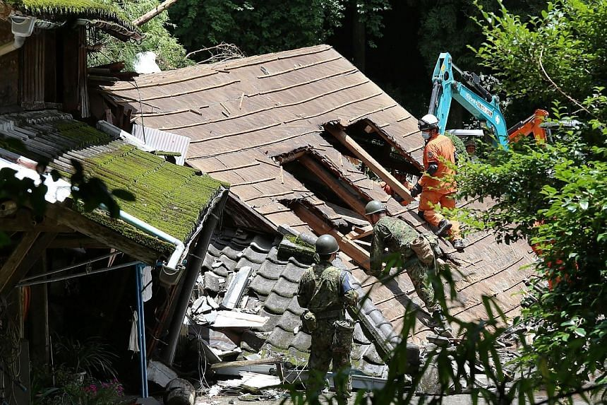 Japan Self-Defence soldiers and firefighters searching for a missing resident in a collapsed house in Kagoshima prefecture, Kyushu Island, yesterday after a landslide caused by heavy rain. PHOTO: AGENCE FRANCE-PRESSE