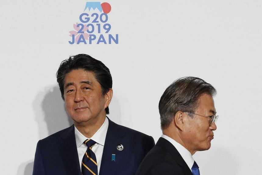 Japanese Prime Minister Shinzo Abe (left) and South Korean President Moon Jae-in at the G-20 summit in Osaka on June 28, 2019. They failed to hold a customary one-on-one meeting at the summit.