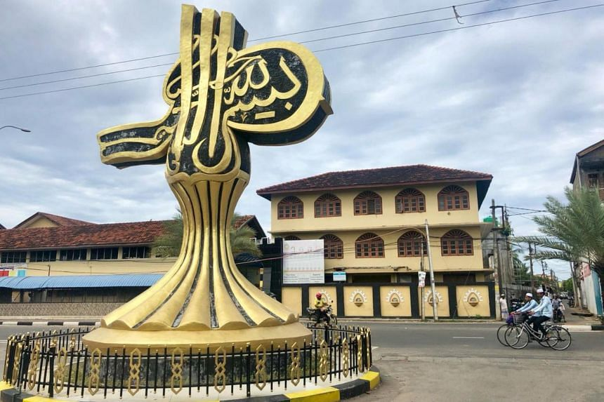 """Muslim boys ride their bicycles past a sculpture in Kattankudy, Sri Lanka on June 10, 2019. The Arabic scripture reads """"In the name of God""""."""