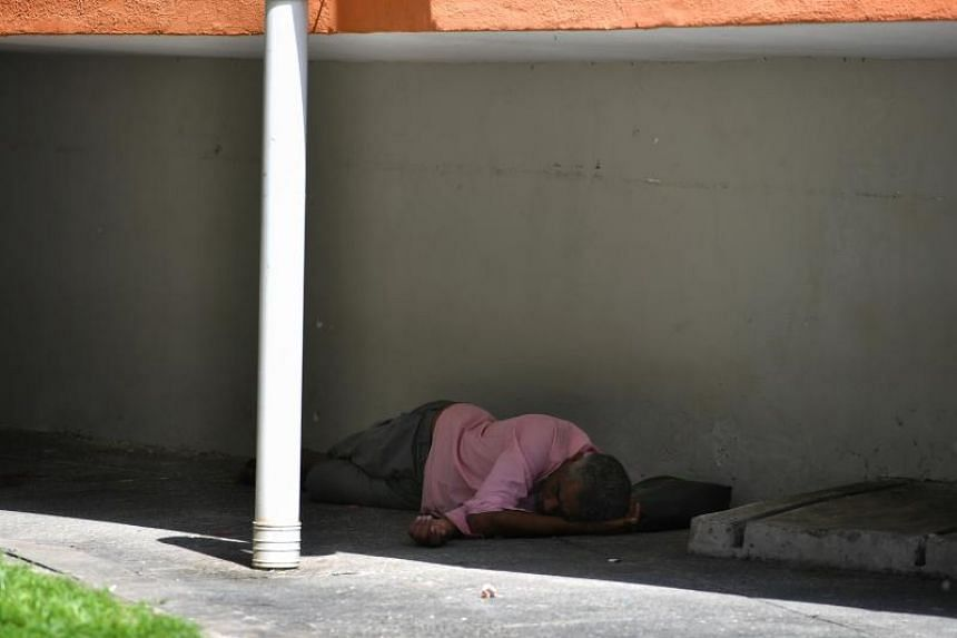 An old man sleeps in a shaded area of an HDB block at a Chin Swee HDB estate.