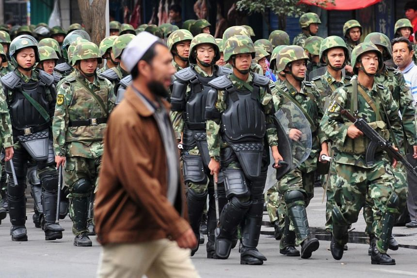 Armed Chinese soldiers marching on patrol as an Uighur man crosses the street in Urumqi, in north-west China's Xinjiang province on July 15, 2009.
