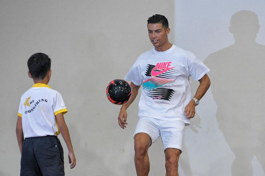 Footballer Cristiano Ronaldo juggles a ball on stage during his visit to meet both Chongzheng and Yumin Primary School students in support of the Singapore Olympic Foundation-Peter Lim Scholarship on July 4, 2019.