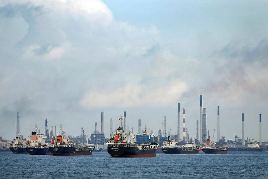 Ships anchored in front of a refinery on Singapore's Pulau Bukom in the Malacca Strait on July 6, 2014.