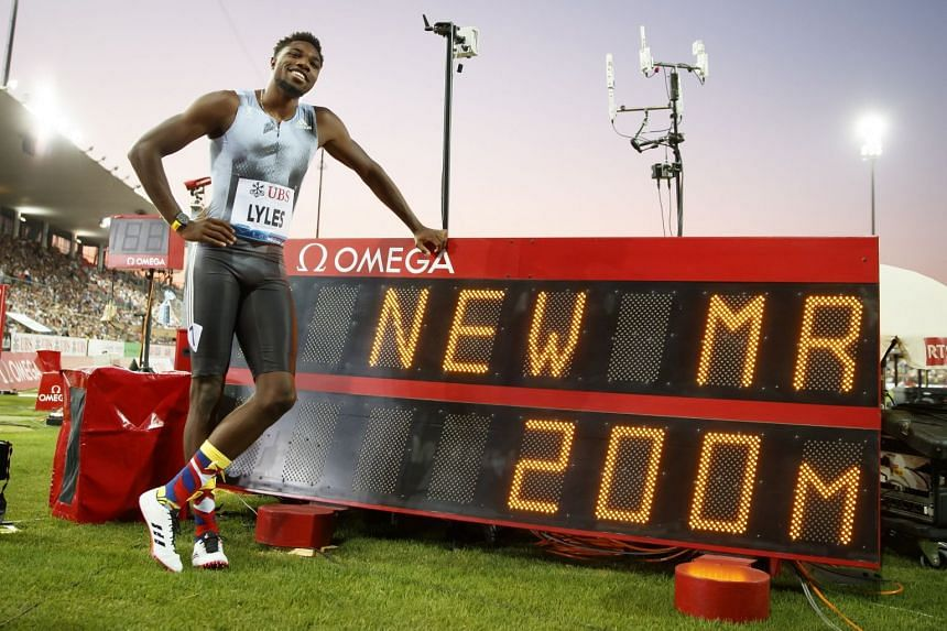 Noah Lyles poses next to an electronic display after winning the men's 200m race.