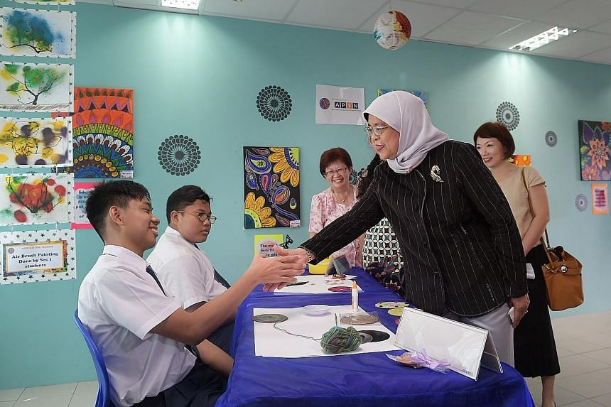 Right: The Istana Cookies were launched yesterday. Far right: President Halimah Yacob with students Joel Tan (at left), 16, and Afiq Rifdi Jaidi, 14, at the Association for Persons with Special Needs Katong School yesterday.