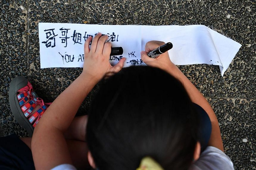 Top and above: Thousands of women, mostly mothers, but also a number of men who wanted to lend their support, gathering at Chater Garden in Hong Kong yesterday to show solidarity with the young protesters. Left: A young child writing a message encour