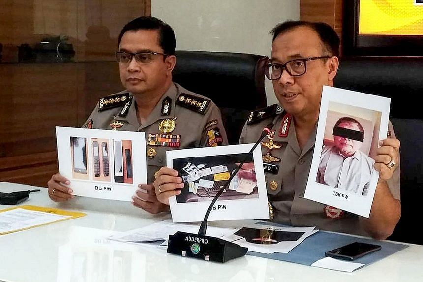 Indonesian police with photographs of Neo-JI leader Para Wijayanto and various seized items in Jakarta on Monday. The militant was arrested last Saturday, after 16 years on the run. PHOTO: AGENCE FRANCE-PRESSE