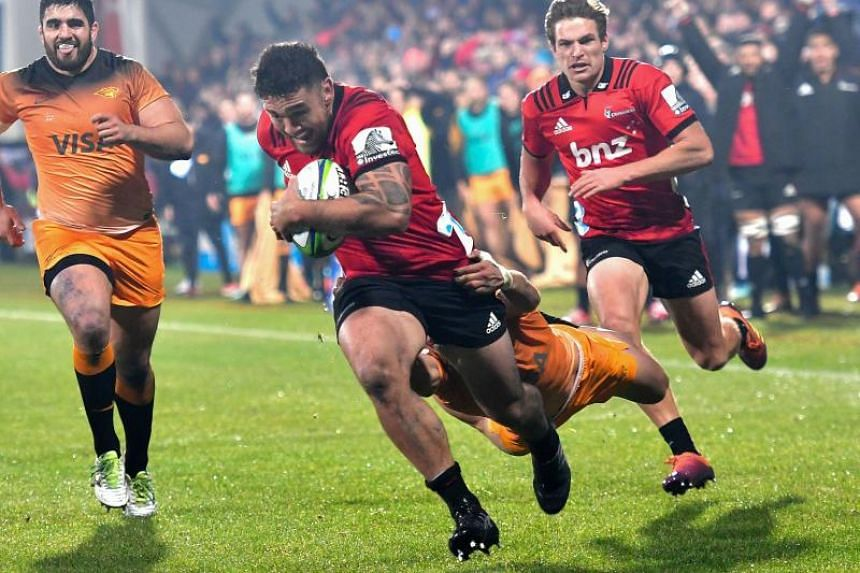 Crusaders' Codie Taylor (with ball) runs in a try as he is tackled by Jaguares' Matias Orlando in Christchurch, New Zealand, on July 6, 2019.