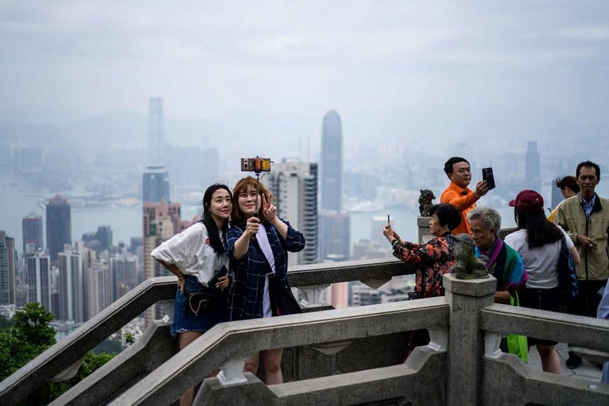 Tourists take selfies at Victoria Peak, in front of a view of residential and commercial buildings in Kowloon and Hong Kong island (foreground), separated by Victoria Harbour.