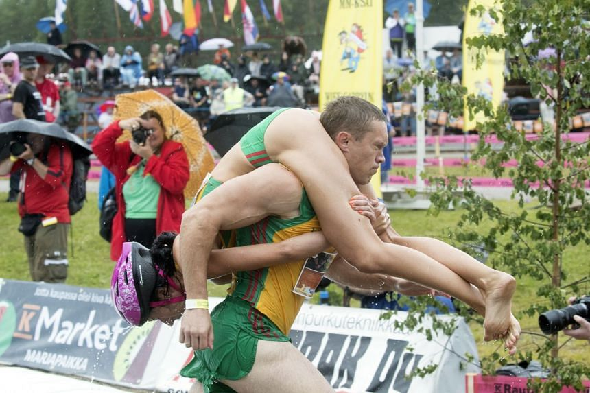 Competitors Kirkliauskas Vytautas and Kirkliauskiene Neringa of Lithuania participate in the annual Wife Carrying World Championships.