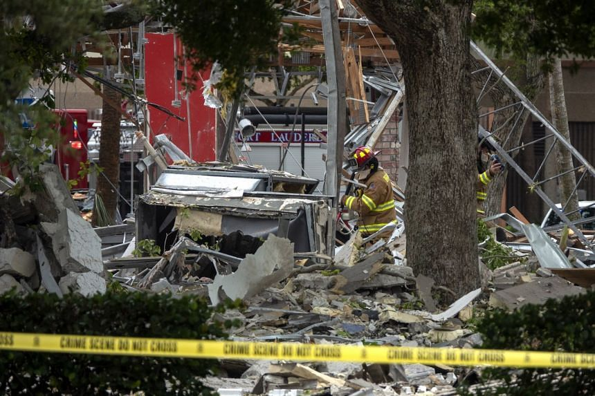 Firefighters work in the area where an explosion occurred at a mall in Plantation, Florida.