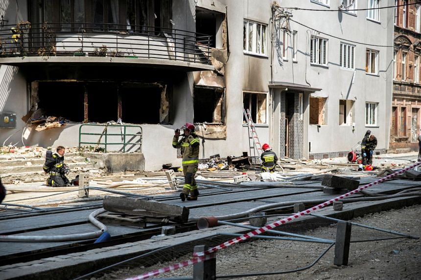 Firefighters work at a site of an explosion in a residential building in Bytom, southern Poland.