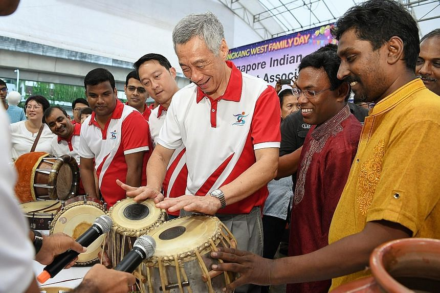 Prime Minister Lee Hsien Loong trying out the tabla, a traditional Indian percussion instrument, yesterday at the Sengkang West Family Day, as Senior Minister of State for Health and Transport, and MP for Sengkang West, Dr Lam Pin Min, looks on. With