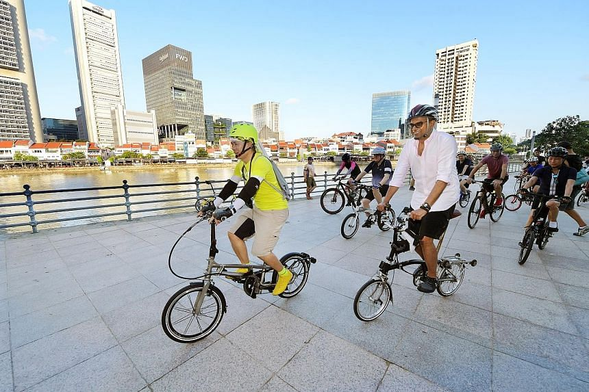 Mr Han Jok Kwang, trustee of The Straits Times School Pocket Money Fund (SPMF), and Dr Janil Puthucheary, Senior Minister of State for Transport and Communications and Information, leading the pack at a charity cycling event yesterday at Marina Bay.