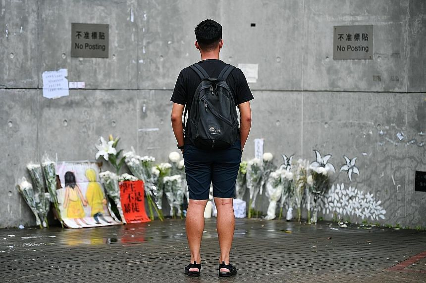 Events organiser Adrian Lam standing at the memorial at Lennon Wall near the Central Government Complex in Admiralty, Hong Kong. Protest artwork and post-it notes have been torn down and all that remains are bouquets to commemorate the three people w