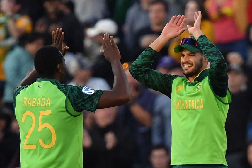 South Africa's Aiden Markram (right) celebrates with teammate Kagiso Rabada after taking a catch to dismiss Australia's Alex Carey.