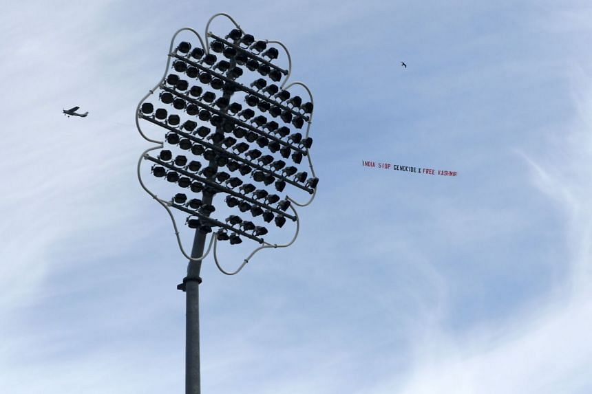 """A light aircraft tows a banner with the words """"India Stop Genocide & Free Kashmir"""" during the match."""