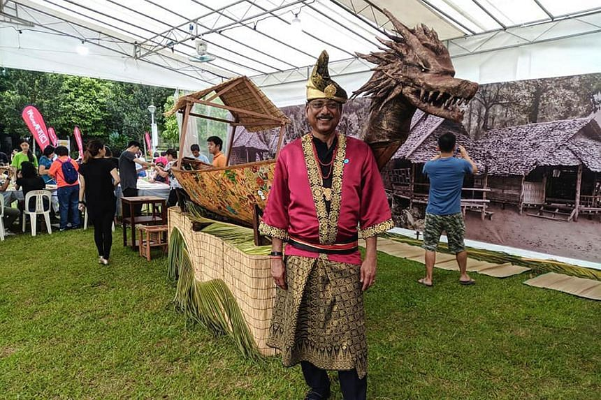 A volunteer dressed in traditional Malay garb with a sampan at the PAssionArts Festival on July 7, 2019.