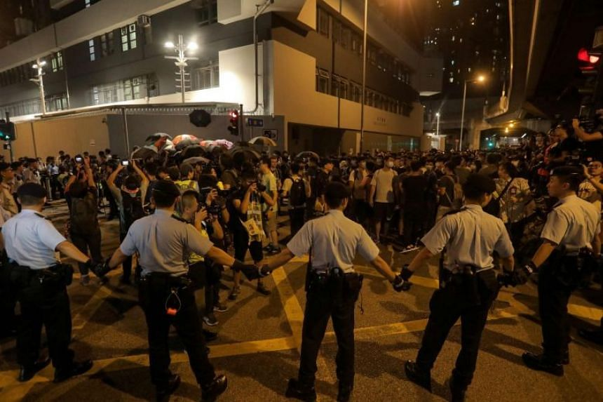 Policemen hold hands to line up and surround protesters during the Tuen Mun protest.