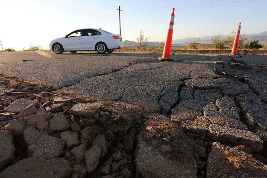 A car passes over a fissure that opened on a highway during a powerful earthquake that struck Southern California on July 4, 2019.