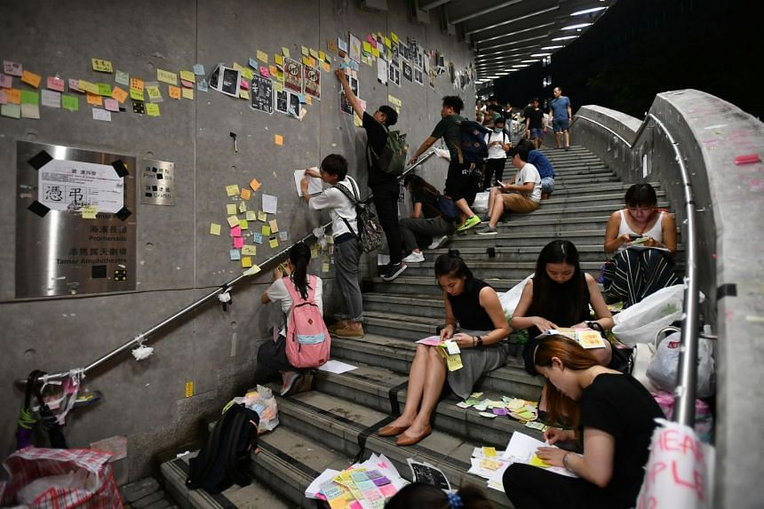 """People removing Post-it notes with messages about democracy and universal suffrage from the """"Lennon Wall"""" at the Central Government Complex in Hong Kong on July 2, 2019."""