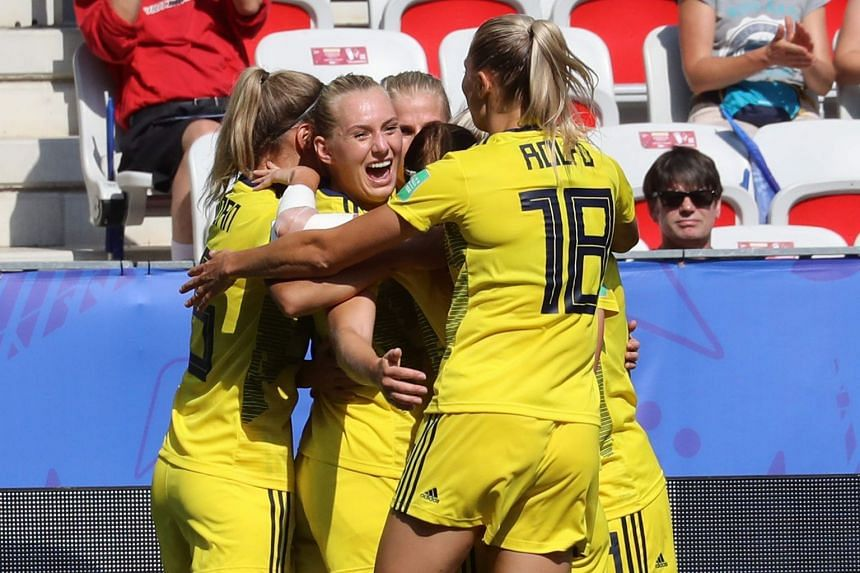 Sweden's midfielder Kosovare Asllani (hidden) is congratulated by teammates after scoring.
