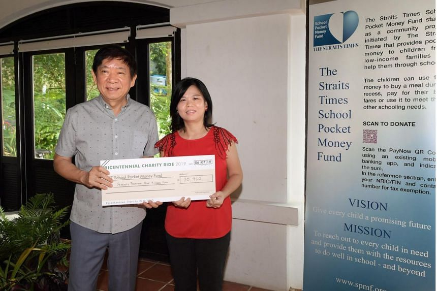 Minister Khaw Boon Wan presenting the cheque to Ms Tan Bee Heong, General Manager of the Straits Times School Pocket Money Fund on July 6, 2019 at the Raffles House at Fort Canning Park.