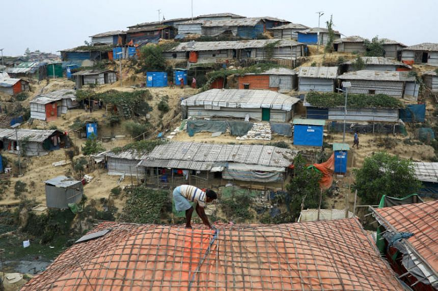 A Rohingya man repairing the roof of his shelter in the Balukhali refugee camp in Cox's Bazar on March 5. Monsoon-triggered landslides in refugee camps around Cox's Bazar have killed one and left thousands homeless.