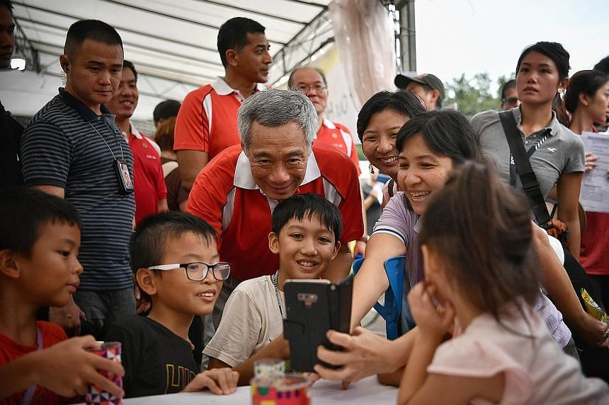 Above: Prime Minister Lee Hsien Loong taking a wefie with residents at Bishan-Ang Mo Kio Park yesterday. Left: Zentai performers entertaining visitors at the first festival village for the PAssionArts Festival.