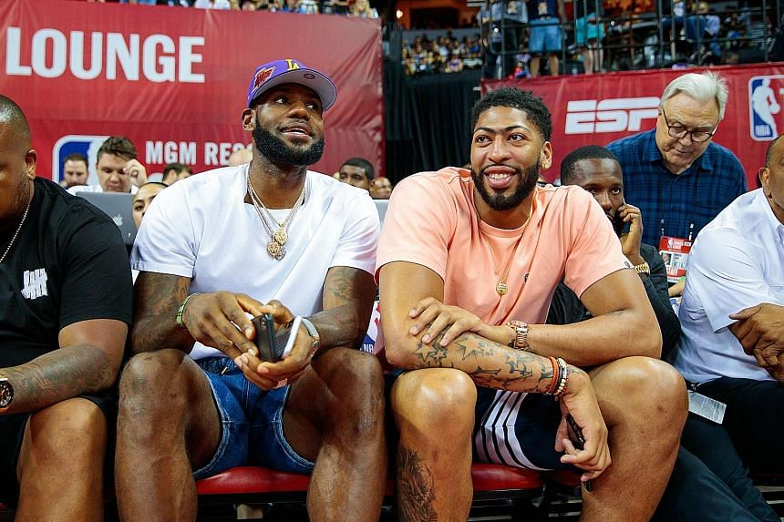 Los Angeles Lakers forward LeBron James (with cap) and his new teammate Anthony Davis watching an NBA Summer League game in Las Vegas between Davis' former team, the New Orleans Pelicans, and the New York Knicks.