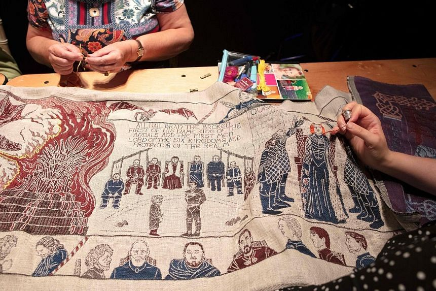 """Seamstresses working on the final section of a tapestry depicting the gory battles of hit television series Game of Thrones at Ulster Museum in Belfast. The tapestry, woven of fine linen, includes the show's icons, like its """"blood red weddings"""" and """""""