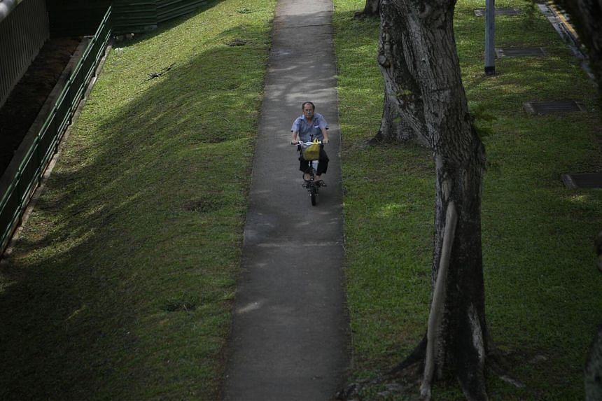 An elderly man rides his e-scooter along the pavement near Bishan MRT Station.