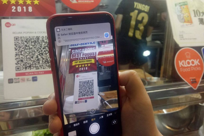 A patron using SGQR to pay at a food stall. McKinsey consultants said in May that seven in 10 Singaporeans use a digital wallet and transaction volumes are growing daily.