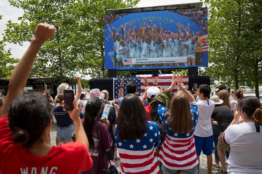 US players seen on a screen celebrating, as fans watch the France 2019 Women's World Cup final football match between US and the Netherlands, in Washington on July 7, 2019.