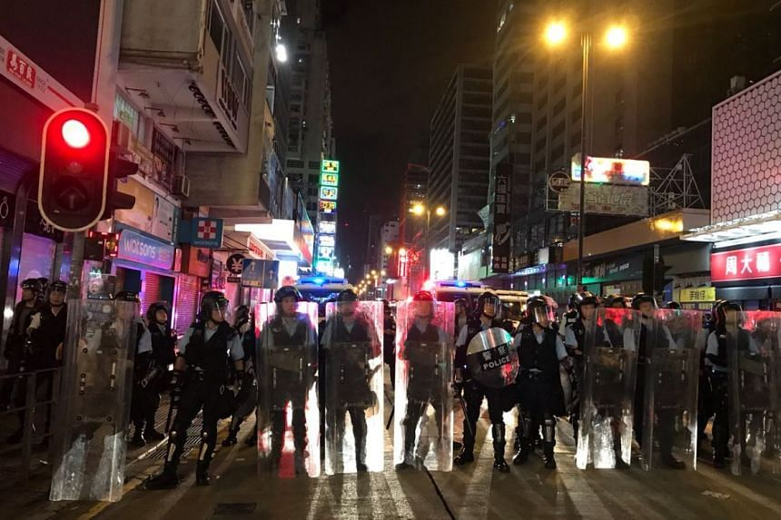 Hong Kong police face off with protesters in the Mong Kok district at night on July 7, 2019.
