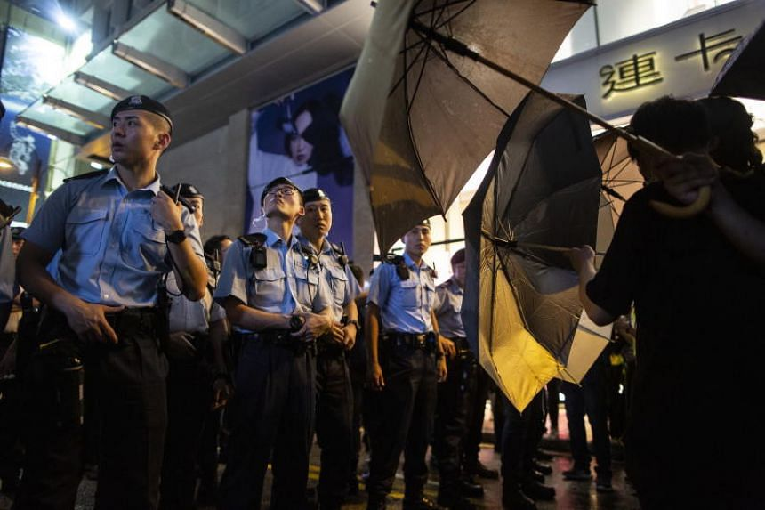 Anti-extradition bill protesters stand with umbrellas in front of the police after taking part in a march in Hong Kong, on July 7, 2019.