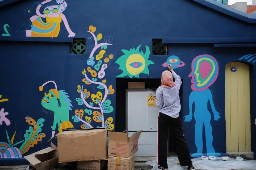 An artist paints a mural in the Muscat Street/Kampong Glam district, on June 18, 2019.