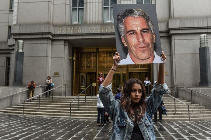 """A protest group called """"Hot Mess"""" hold up signs of Jeffrey Epstein in front of the federal courthouse in New York on July 8, 2019."""