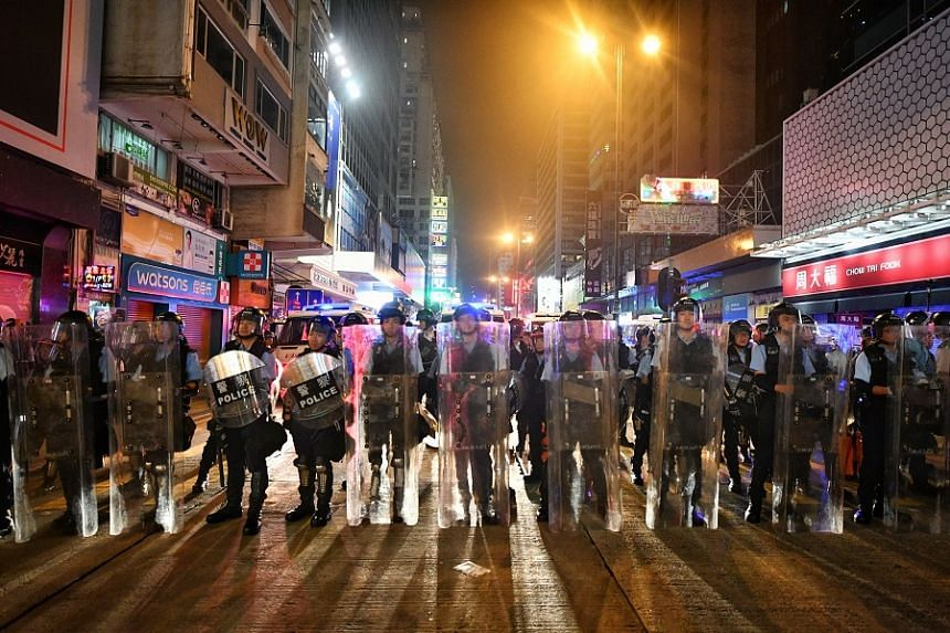Hong Kong police in the city's Mong Kok area on July 7. Six people were arrested for assaulting and obstructing a police officer when action was taken to disperse protesters. PHOTOS: ST FILE, BLOOMBERG, REUTERS