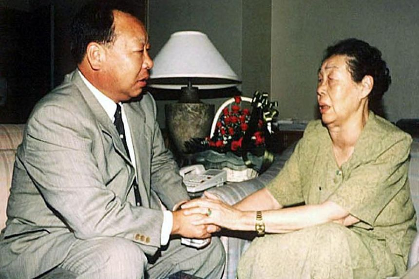 """Choe In-guk, seen here in an August 2000 picture with his mother Ryu Mi Yong, had failed to secure a stable job after his parents' defection to North Korea and could not shake the """"infamous"""" association at a time of intense rivalry between Pyongyang"""