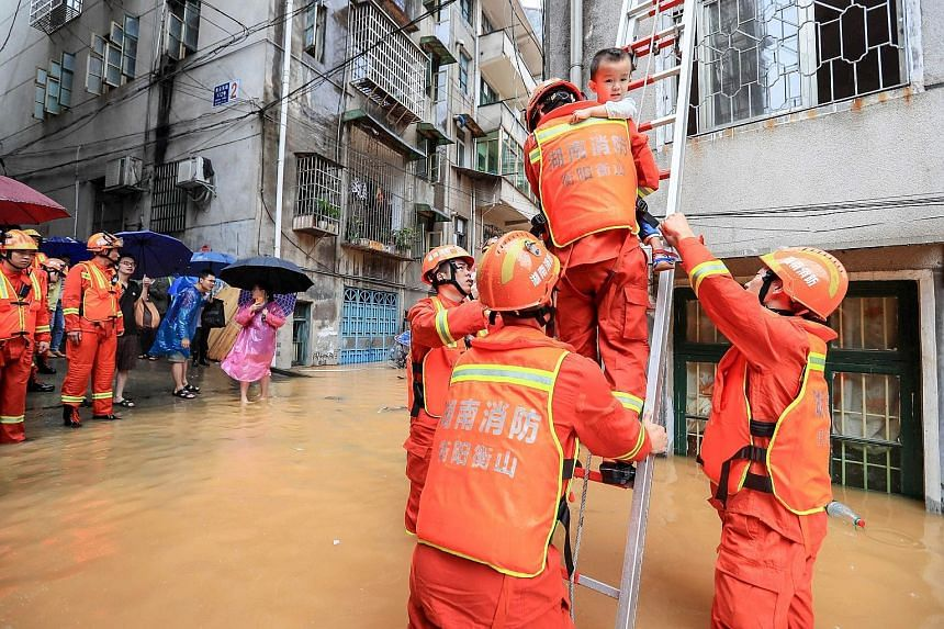 Rescuers evacuating a child from a building in a flooded area after heavy rain in Hengyang, China's Hunan province, yesterday. PHOTO: AGENCE FRANCE-PRESSE Residents of Alor Gajah in the Malaysian state of Melaka have started cleaning up after floods