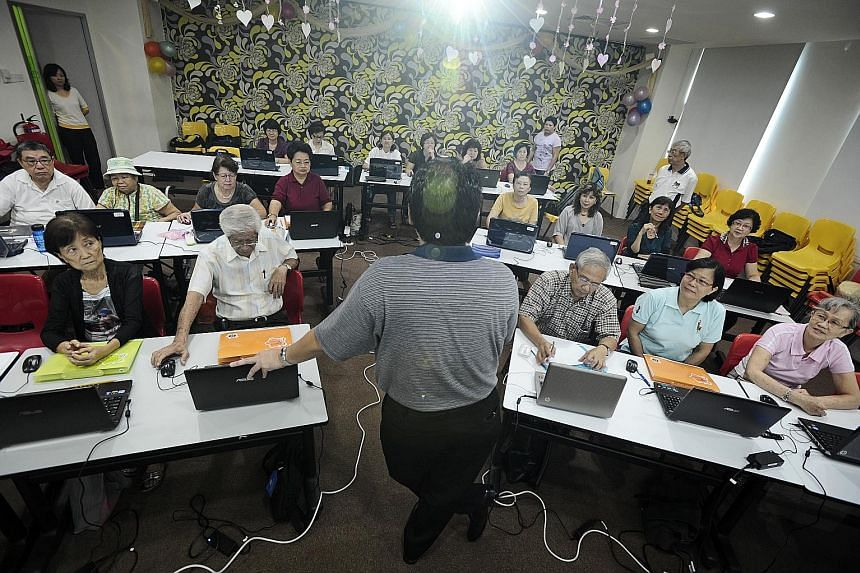 Seniors attending a computer class conducted by a community group. The new Merdeka Generation digital clinics supplement existing educational efforts and are expected to reach about 10,000 seniors over one year.