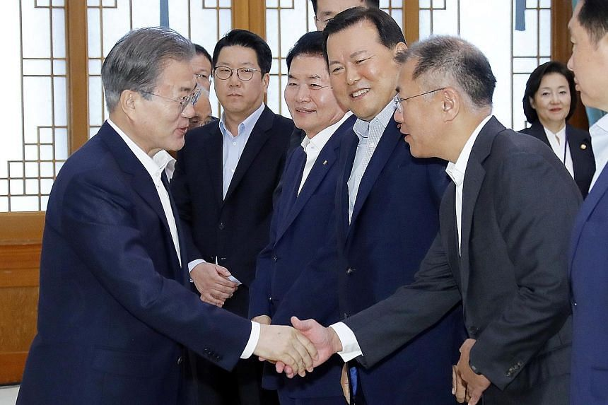 South Korean President Moon Jae-in (far left) shaking hands with Hyundai Motor executive vice-chairman Chung Eui-sun at a meeting with the country's top 30 conglomerates yesterday, where Mr Moon promised to provide active support for domestic product