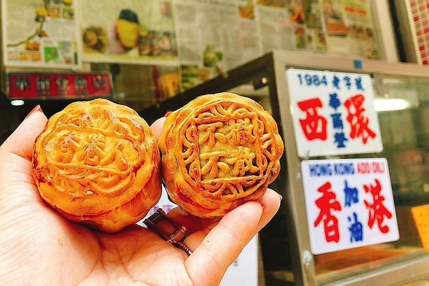 "Mooncakes from the Wah Yee Tang Cake Shop that read ""Hong Kongers"" (far left) and ""no withdrawal, no dispersal"". The mooncakes have sold out every day since the shop began offering them on Monday."