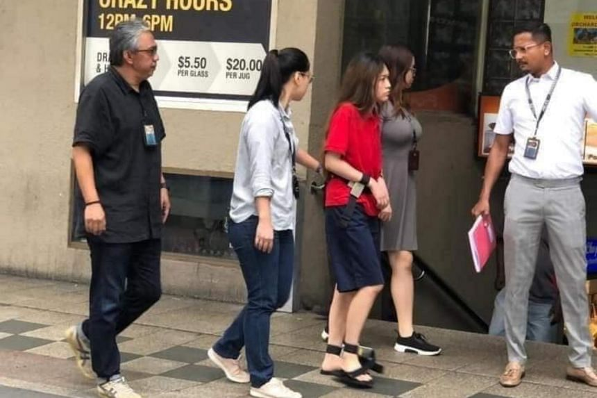 Suspect Natalie Siow Yu Zhen (in red) was among the suspects taken back to the murder scene at Orchard Towers on July 9, 2019.