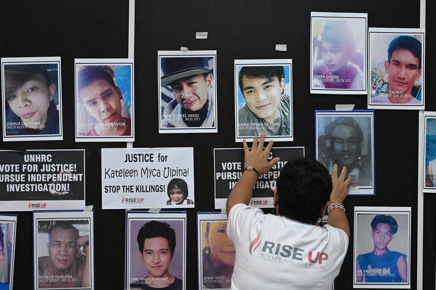 A relative of a victim of an extrajudicial killing touches the portrait of the relatives during a memorial mass at the Philippine Human Rights Commission office in Manila on July 9, 2019.