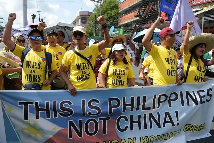 Protesters carrying placards shout anti-China slogans during a rally in Manila, on July 9, 2019.