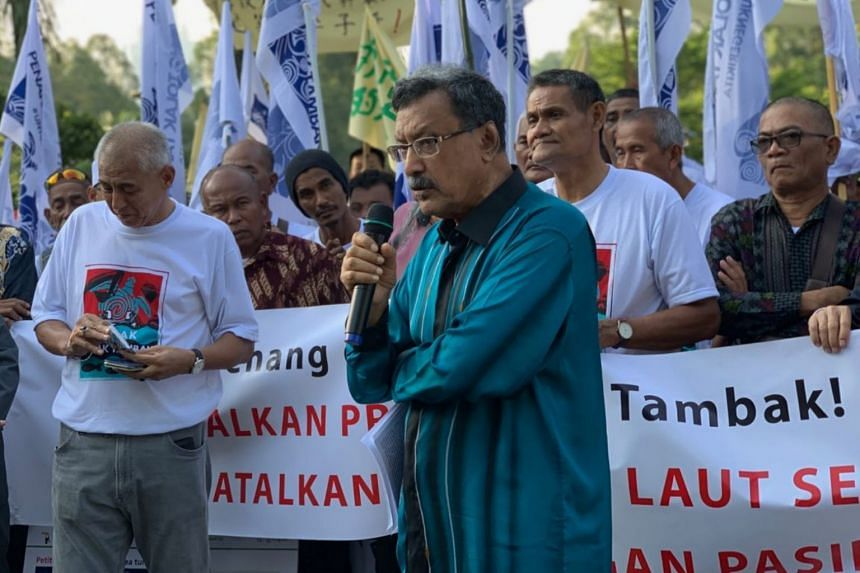 Mr Mohideen Abdul Kader, Consumers Association of Penang president, explaining how the reclamation will affect prices of seafood, at a rally near Parliament in Kuala Lumpur on Thursday.